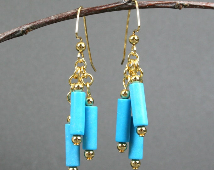 Turquoise blue magnesite dangle earrings with gold plated ear wires, chain, and beads