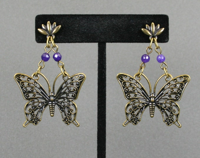 Antiqued brass butterfly and amethyst dangle earrings on antiqued brass lotus flower ear studs