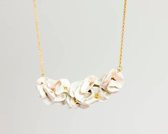 Floral ceramic necklace. White and pink with gold detail.