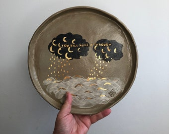 """Ceramic plate with cloud and sea, and real gold detail, and with the inscription """"you will make it through"""""""