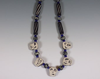 Dia de los Muertos handmade Day of the Dead Necklace with carved bone Skeleton faces in blue, black, and white.