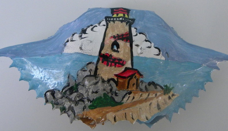 Old brick and mortar lighthouse on a pile of rocks hand painted on to a Christmas crab shell ornament
