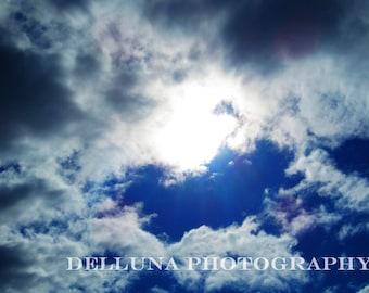 Inspiring photo of sun breaking through white clouds across a stunning blue sky.