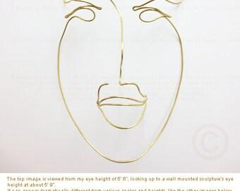 "Metal wire wall sculpture of a man's face   6"" width x 9.4"" height x 2.5"" in depth. Medium: 14 gauge Brass wire. © Theo J Huckins"