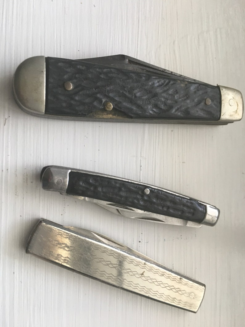 Set of 3 knives Sabre Revlon Pocket Knives and one that is not Marked