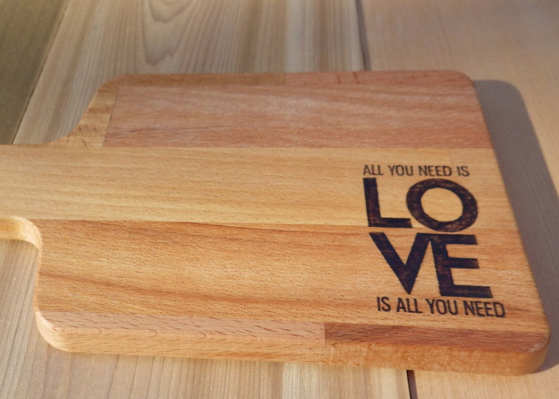 All you need is love Solid Beech Cutting Board with Woodburning Illustration of Classic Saying love is all you need