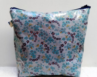 Cotton toiletry bag coated with blue flowers on a gray background