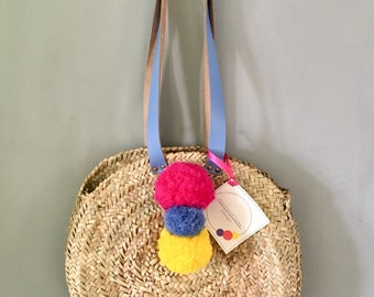 Circular basket bag with leather handles and pompom decoration