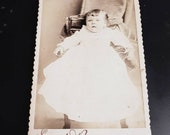 Vintage Victorian photograph of a little baby girl in a long white dress