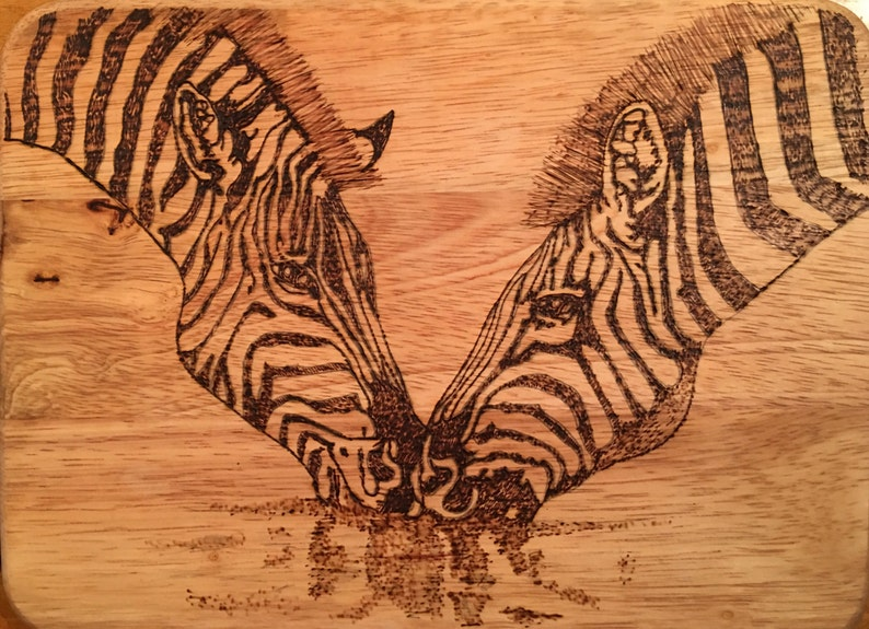 Small cutting board wood burned with 2 zebras drinking water.