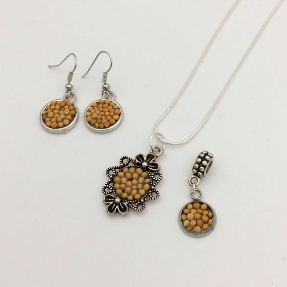 JW Mustard Seed Jewelry Set, featuring Dainty Pendant filled with organic mustard seeds. Matching earrings and bracelet charm.