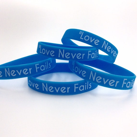"The ""Love Never Fails"" Silicone Wristbands in Blue or Black,  Lot of 1, 5, 10, 50 or 100 available.  Great gift idea!"