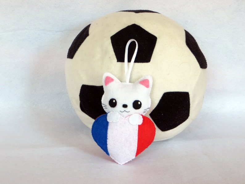 Cat plush in a heart in the colours of the French flag in image 0