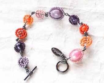 Bright orange, violet, lilac and soft pink beaded bracelet