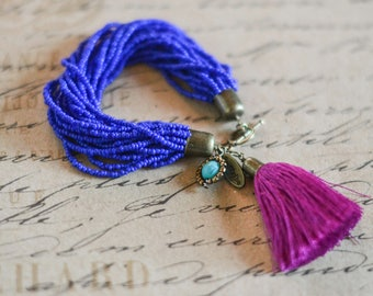 Multi-stranded beaded bracelet in a rich royal blue with magenta tassel and turquoise beaded charm