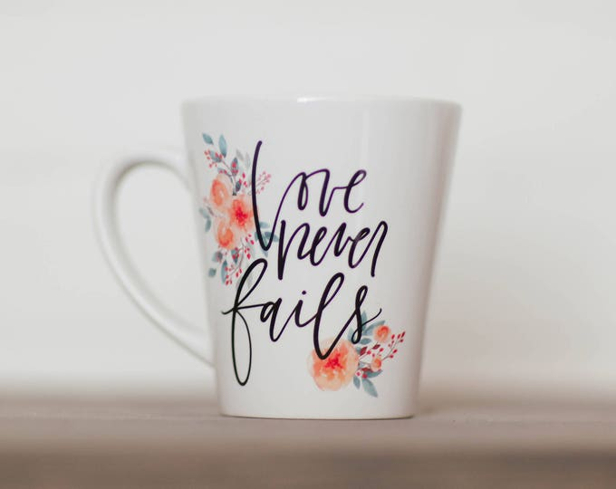 Featured listing image: Love Never Fails || Hand Lettered Coffee Mug