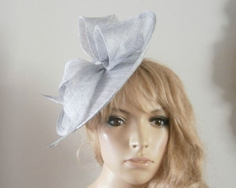 hand made metallic silver sinamay saucer hat with sculptured now detail.