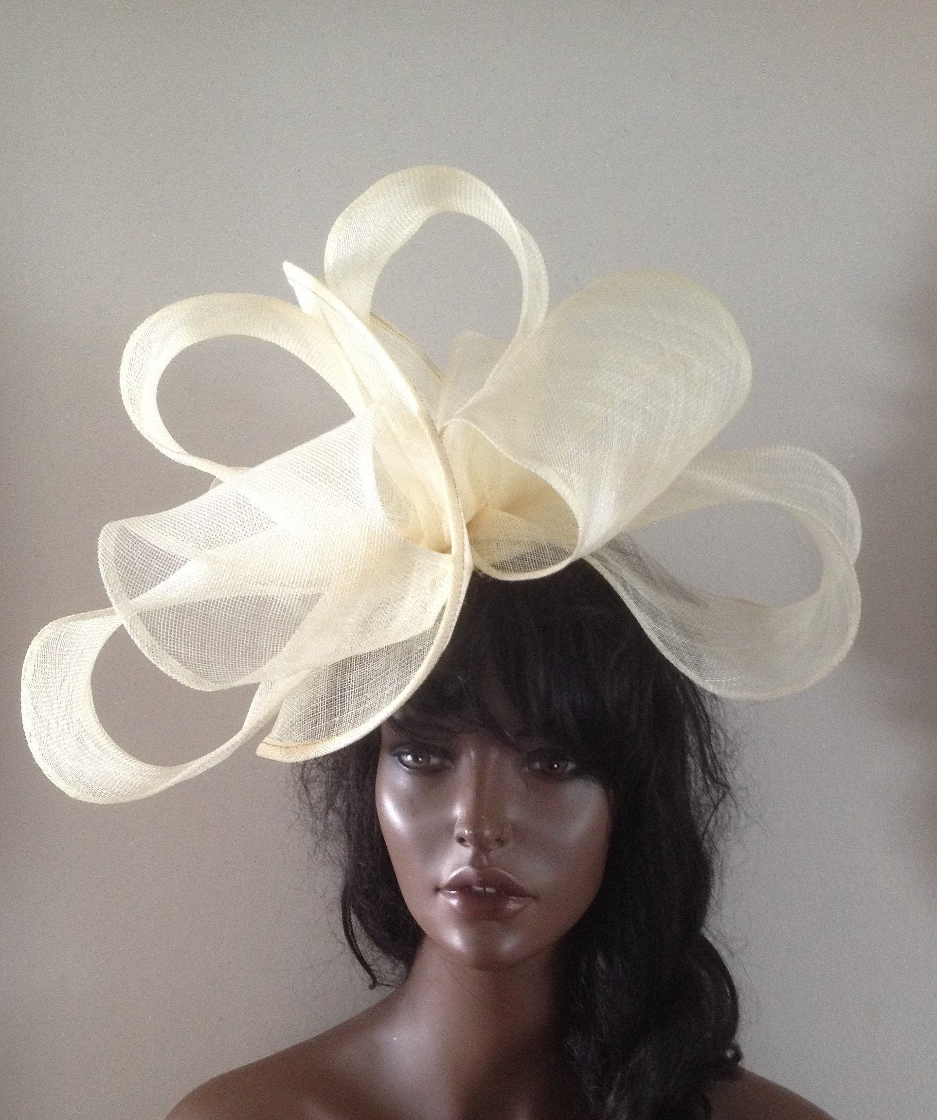 d1e7a26df9ee2 Cream coloured sinamay twisting fascinator hat adorned with hand ...