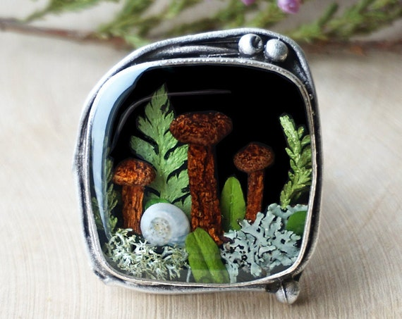 Forest ring with real mushrooms, green leaves, lichens, fern, heather and a tiny snail shell.