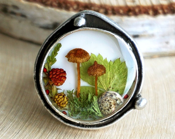 Nature ring with real mushrooms, wild strawberry leaf and berries, heather and snail shell.