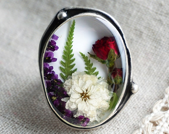 Botanical ring with Real Viola, green leaves, Buttercup, Alyssum and Forget me not flowers.