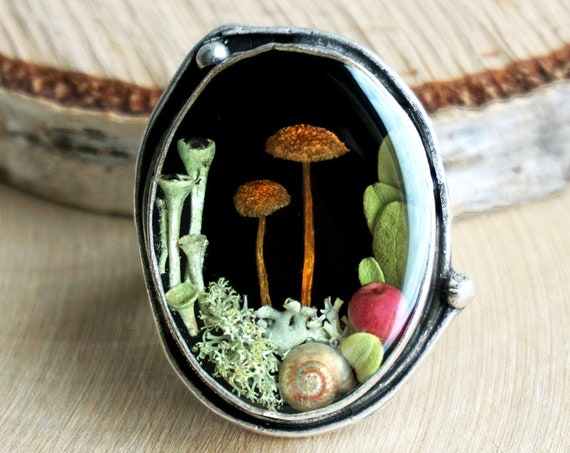 Forest ring with real mushrooms, cranberry leaves, lichens, pink berry and a tiny snail shell.