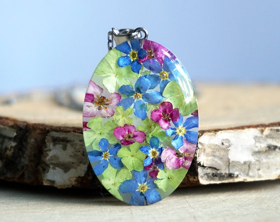 Botanical pendant with Real Alyssum, Viburnum and Forget me not flowers.