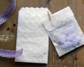 10 White embossed bags in glassine paper
