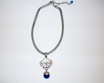 Stylish silver tone necklace accented with Etruscan design pendant. Flexible double chain.
