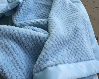 A lovey blanket in a Beautiful baby soft and plush single layer fleece baby blanket with satin binding  blue