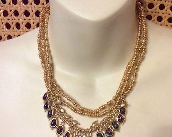 Vintage triple strand gold toned metal beads purple cabachon dangles necklace.