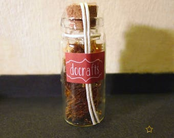 Glass vial filled with little stars gold
