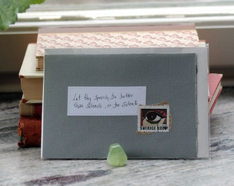 Let thy speech be better than silence, or be silent Grey card with handwritten quote and Swedish eye postal stamp