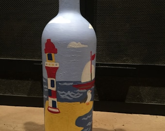 Recycled, painted wine bottle with a lighthouse, & sailboat  scenery on it with lights inside