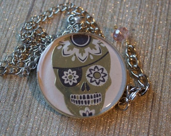 Gold foil pirate sugar skull pendant necklace on a pale pink background sealed in clear resin // gifts for her // creepy cute // halloween