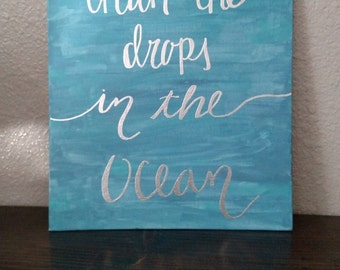 Drops in the Ocean quote, embossed in silver, painted on canvas.