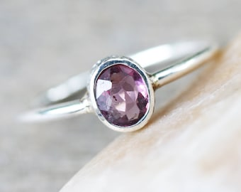 Oval red/purple spinel ring in silver bezel setting with sterling silver high polish finished band