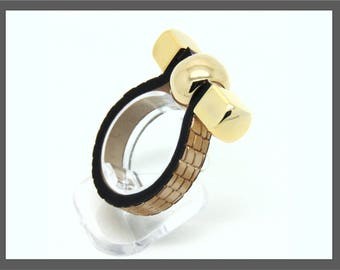 Chunky gold or silver ring with faux leather band and rounded end-studs. This is simple but very distinctive.