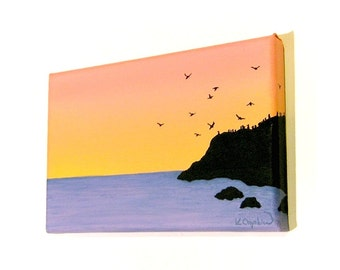 Orange Dawn original seascape - small acrylic painting with the silhouette of sea birds flying around a cliff, orange sky over purple sea
