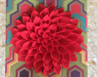 Bright red felt Dahlia mounted on a multi colored background!