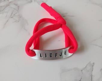HANDMADE Armbandje van roodroze jersey stof met handgemaakte aluminium tag met tekst: liefje (op voorraad)