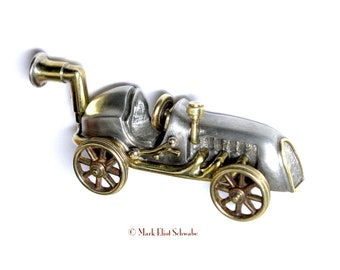 Grand Prix race car reimagined; a brooch with 5 moving parts, It comes with a frame so that you can display it when you are not wearing it