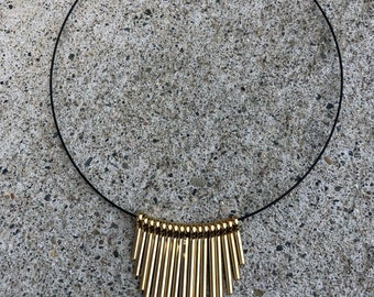 Wire choker with golden accent pendant.