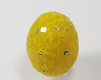 Yellow egg covered with multicoloured porcelain with geometrical pattern and small pieces of tile