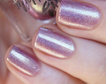 "Nail polish - ""Streams Of Gold"" A light pink foil holo with gold to green shifting shimmer."