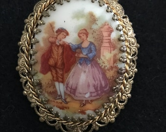 Vintage brooch with intricate goldtone backing and limoges fragonard design of a courting couple.