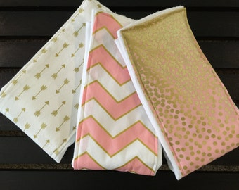 Baby girl burp cloths in blush pink, white, and gold glitz chevron, arrows, and confetti on Oso Cozy diaper