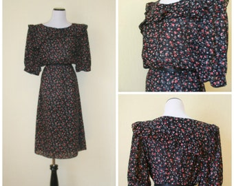 Early 80s prairie dress by Charlee Allison for Eljay, modern calico floral print, diagonal pioneer front-back hit of ruffle on bodice. M-L.