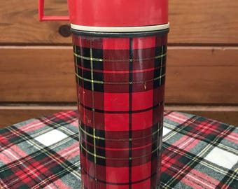 Vintage metal red,black and yellow plaidThermos with plastic red lid.