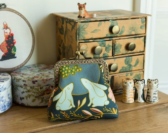 Coin purse made with a moon gazing hares print and a golden metallic lining, with a hand stitched bronze colour metal frame